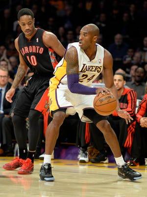 Lakers guard Kobe Bryant dribbles against Raptors guard DeMar DeRozan in Sunday's Los Angeles loss.