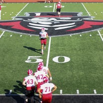 Austin Peay State University football team warms up before the first day of spring football practice on Monday.