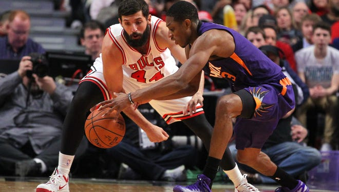 Feb. 21, 2015; Chicago; Chicago Bulls forward Nikola Mirotic (44) and Phoenix Suns guard Brandon Knight fight for the ball during the second half at the United Center.