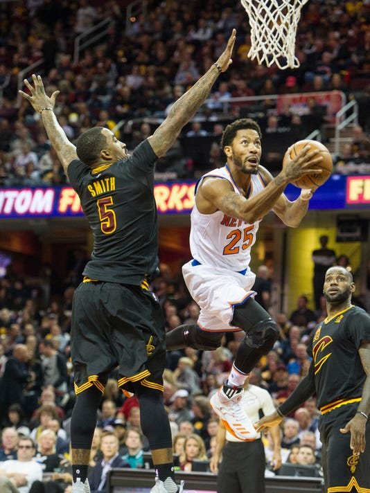 New York Knicks' Derrick Rose (25) drives past Cleveland Cavaliers' J.R. Smith (5) as the Cavaliers LeBron James watches during the first half of an NBA basketball game in Cleveland, Tuesday, Oct. 25, 2016. (AP Photo/Phil Long)