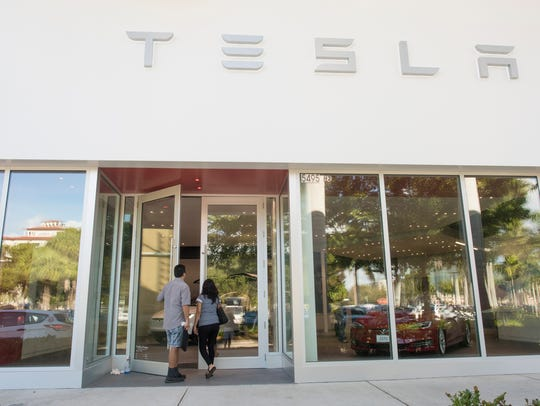 Customers enter the new Tesla store at Waterside Shops