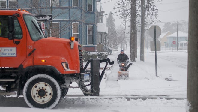 Russ Kelly snow blows the sidewalks as a plow truck drives by in Port Huron during a December 2016 snowstorm. The city's snow ordinance starts Friday..