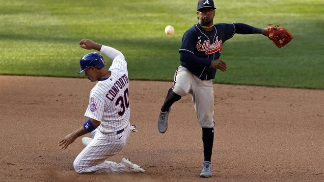Atlanta Braves second baseman Ozzie Albies turns a double play against New York Mets' Michael Conforto (30) during the seventh inning of a baseball game Saturday, July 25, 2020, in New York.