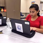 Gulf Middle School eighth-grade students Reimsy Castro and Sheila Madrazo work on their Chromebooks during class.
