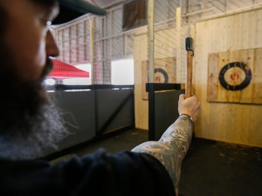 Tom Jennings, owner of TommyHawks Axe House, demonstrates the proper technique for throwing an ax.