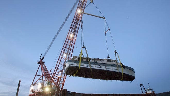 A crane hoists the Eventide onto a barge Monday evening at Bremerton Marina.