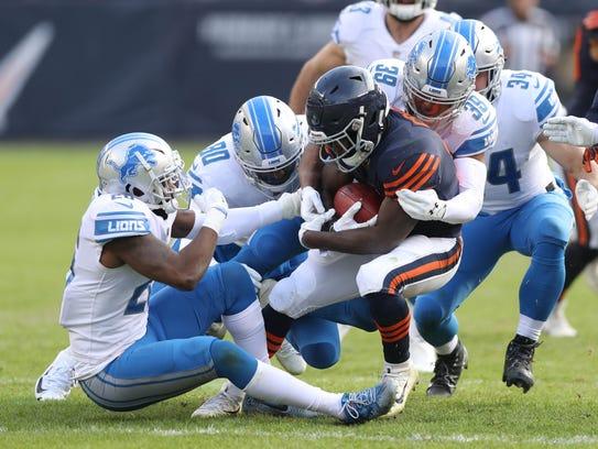 Detroit Lions defenders tackle the Chicago Bears' Tarik