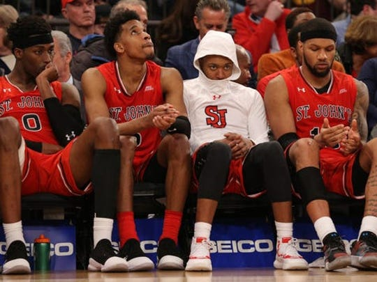 St. John's Red Storm forward Sedee Keita (0) and guard Justin Simon (5) and guard Shamorie Ponds (2) and forward Marvin Clark II (13) react on the bench after getting blown out by Marquette in the Big East tournament.