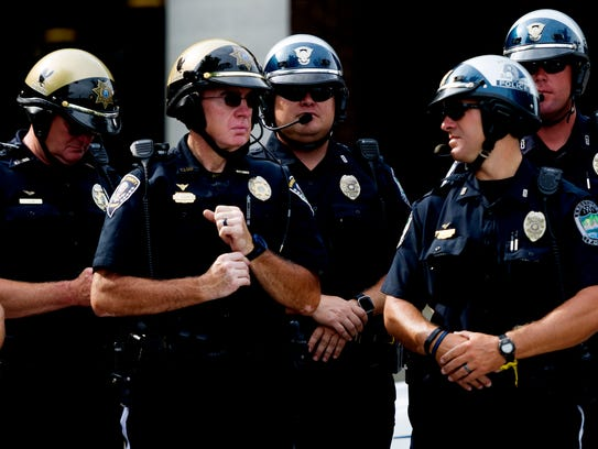 Officers stand by during a press conference on new