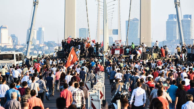 People wave flags as they stand on tanks on the Bosphorus Bridge in Istanbul on June 16, 2016.