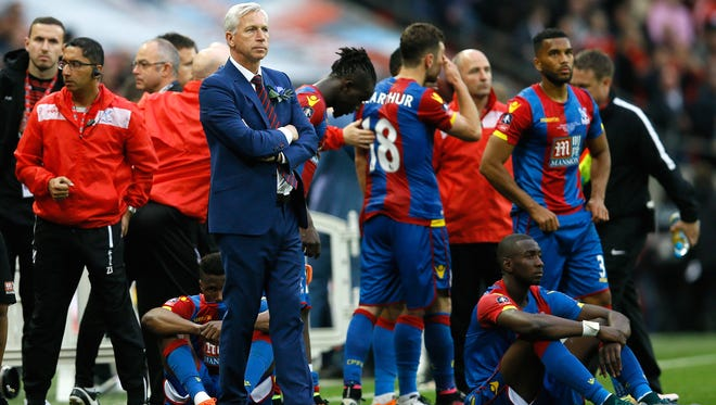 Crystal Palace team manager Alan Pardew and his players react at the end of the English FA Cup final soccer match between Manchester United and Crystal Palace at Wembley stadium in London, Saturday, May 21, 2016. United won 2-1.