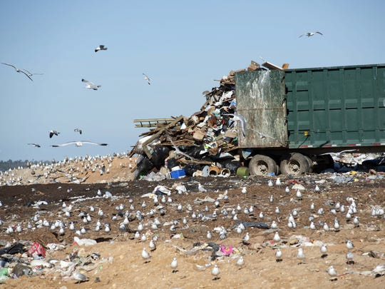A truck offloads garbage and trash at the Perdido Landfill.