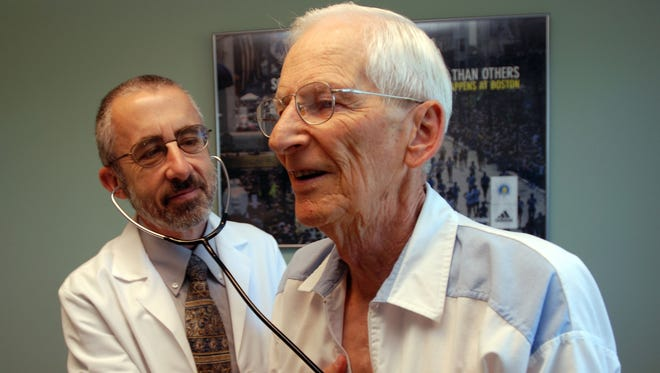 Dr. Bruce Stowell examines patient Robert Busch at his office in Grants Pass, Ore. Opponents of the health insurance mergers say doctors could have faced higher reimbursement cuts