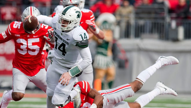 Nov 11, 2017; Columbus, OH, USA; Michigan State Spartans quarterback Brian Lewerke (14) eludes a tackle attempt by Ohio State Buckeyes cornerback Damon Arnette (3) at Ohio Stadium.