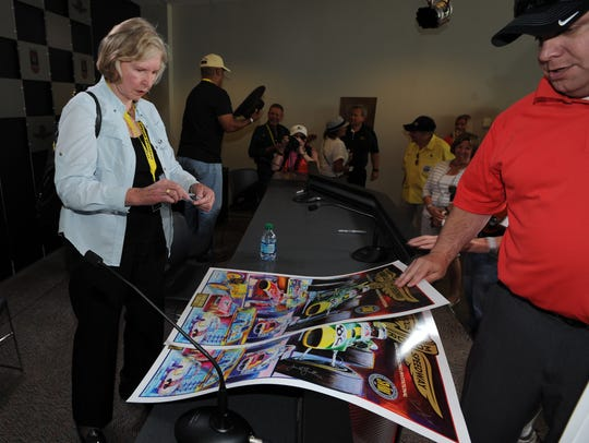 Janet Guthrie signs poster to promo the  up coming