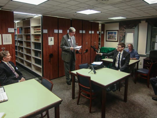 Delcog director John Flaherty reads an excerpt from the LLC reform bill during a Delaware Coalition for Open Government press conference Tuesday.