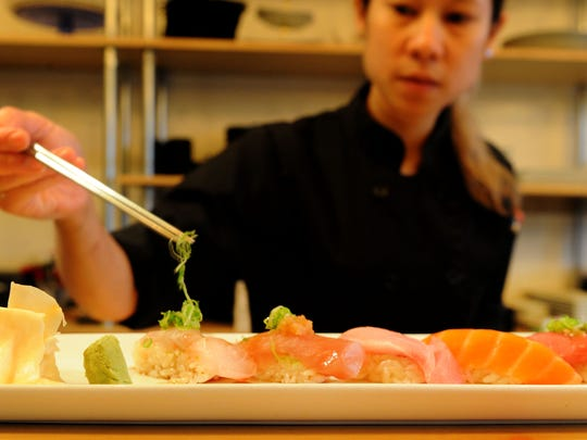 Sushi chef Polly Srisiri prepares a dish at the Prawn