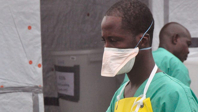 A health worker carries gloves at an Ebola treatment center in the city of Monrovia, Liberia.