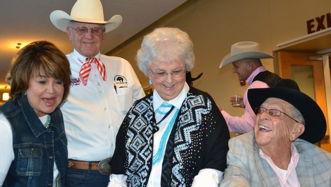 Denny and Geraldine Calhoun, center, co-executive directors of Cowboys For Cancer Research show Rae Ann Paden, left, and Jake Barboa some of the exhibits at this year's Cowboys for Cancer Research dinner dance at the Las Cruces Convention Center