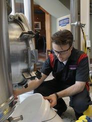 Matthew Kuehn spends a lot of time sanitizing equipment