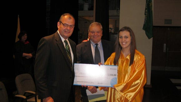 York Catholic's Karli McFatridge, right, receives her $3,500 scholarship from Gretchen Wolf Swartz Scholarship Fund Board of Directors Pat Gebhart, left, and Tom Ryan.