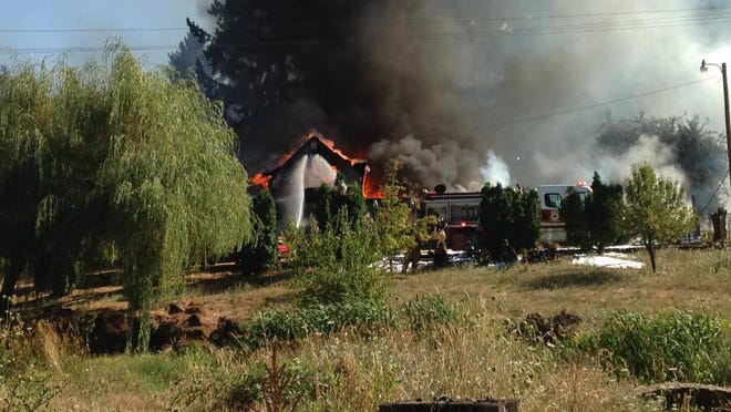 A rural-Scio house fire on Rodgers Mountain Loop erupted amid dry grass and woodlands on an afternoon with temperatures in the 90s, creating challenges for firefighters.