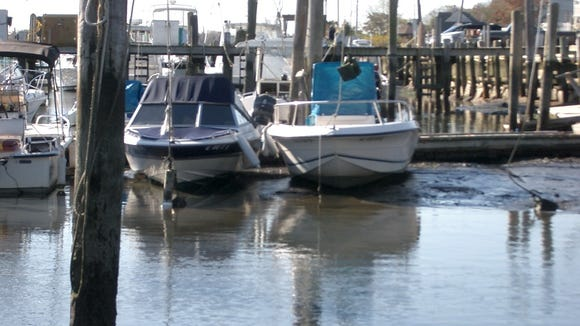An extreme low tide leaves boats stuck in the mud at the Shark River Municipal Marina, where Neptune officials want the state to proceed with a long-awaited dredging project (file photo courtesy Philip Huhn/Neptune Township).