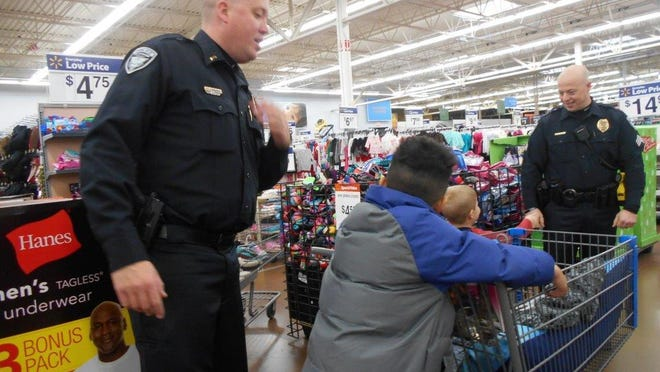 Waukee police Lt. Scott Cunningham, left, and Sgt. Jeremy Long shop for holiday presents with children at Wal-Mart.