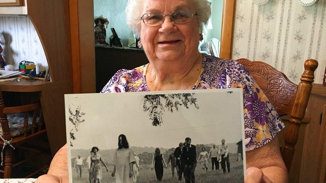 """ADVANCE FOR USE SATURDAY, MAY 12 - In this April 21, 2018 photo, Ella Mae Smith, 86, of Evans City, P.a, poses with a publicity photo from the horror movie """"Night of the Living Dead."""" In the summer of 1968, Ella Mae Smith's skin went pale, and an unholy hunger sent her shuffling through verdant fields in search of human flesh. Today, the whole world's got zombies on the brain, and for the most part, it began when the Smiths and others agreed to be in a low-budget horror film that a bunch of guys from Pittsburgh were making: Night of the Living Dead. (Jason Nark/The Philadelphia Inquirer via AP)"""