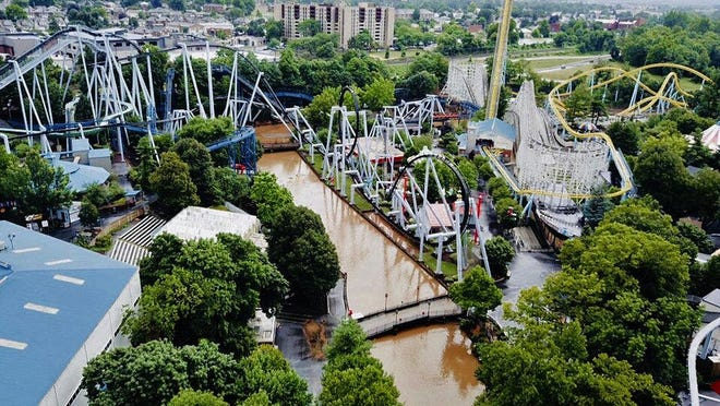 In this Monday, July 23, 2018, aerial image provided by The Wyse Choice photography in Hershey, Pa., muddy brown floodwaters in Spring Creek flow beneath the sooperdooperLooper roller coaster, in blue, and the Great Bear roller coaster, in black, at the Hersheypark theme park in Hershey, Pa. Hersheypark and the neighboring ZooAmerica wildlife park closed due to flooding Monday, July 23, 2018, after three days of rain in the central and eastern parts of Pennsylvania that caused Spring Creek to flood and the nearby Swatara Creek to approach moderate flood stage. (The Wyse Choice via AP)
