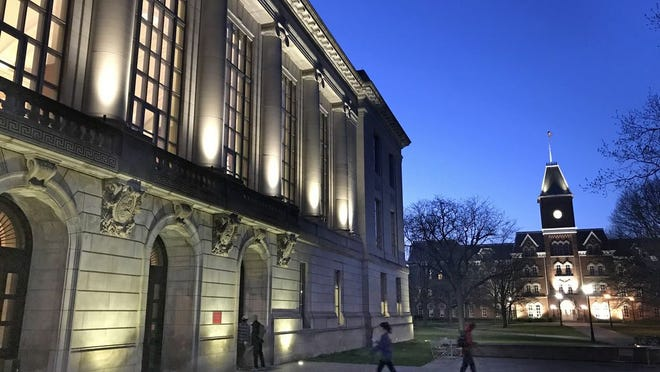 The Thompson Memorial Library is illuminated on the campus of Ohio State University, with University Hall seen in the distance at right. In-person classes have been suspended at Ohio State because of fears of spreading the coronavirus.  [Doral Chenoweth III/Dispatch file photo]