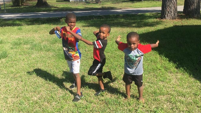 Joshua Bowens, Josiah McCoo and Ryan McCoo play in their front yard after watching Lincoln Elementary School's teacher parade Thursday.