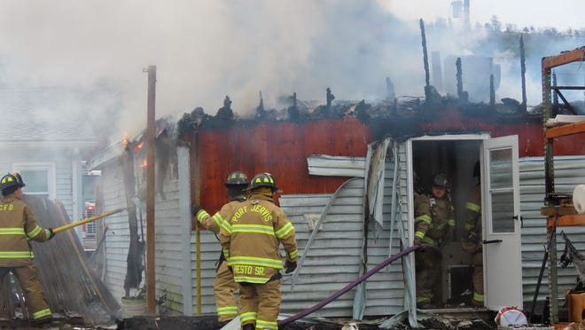 Firefighters at the scene Thursday of a house fire in Huguenot.