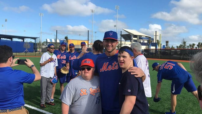 Mets hopeful Tim Tebow poses with a couple special needs children during spring training.