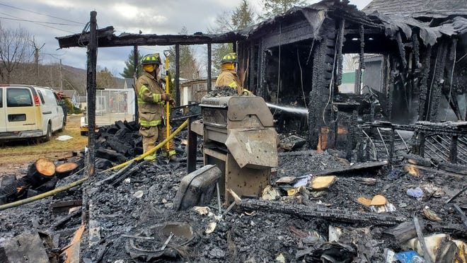 Firefighters put out hotspots at a residential structure fire on Old Silver Pond Road on Sunday in Woodbourne. A family of six was displaced after the fire and is being assisted by the Red Cross.