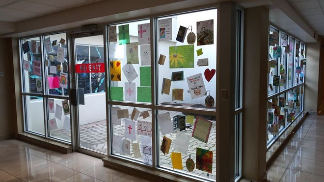 At SSM Health St. Anthony-Shawnee hospital notes of encouragement line the windows inside — sent to offer support and encourage local health care workers during the COVID-19 crisis.