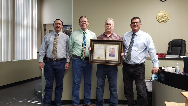 Siskiyou County Supervisors Brandon Criss, Michael Kobseff and Ed Valenzuela stand with Siskiyou County's Community Development Department Deputy Director of Building Michael Crawford (third from left) at a meeting on Aug. 11. He holds a resolution recognizing him for a 34 year career.