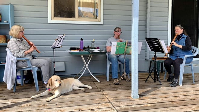 Local musicians sit on a porch in McCloud and rehearse.