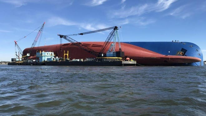 Crews onboard work barges provide a platform for personnel and equipment to prepare the capsized Golden Ray ship for removal.
