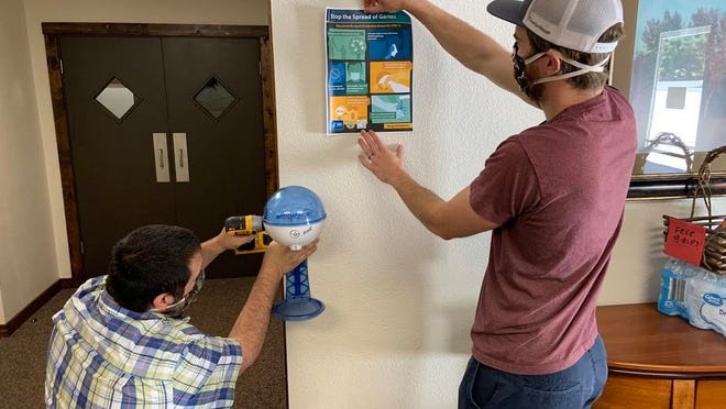 Mount Shasta First Baptist Church pastor Brandon Turk, left, and pastor Alastair Curley work to install a new hand sanitizing station in the church in preparation for their first in-house service in months.