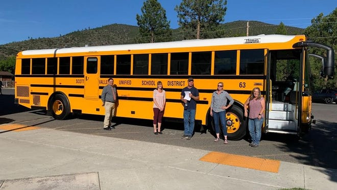 Dianne Hasemeyer, Transportation Supervisor for the Scott Valley Unified School District, far right, stands in front of a new bus the district purchased with grant funding from the Siskiyou County Air Pollution Control District. She is joined in the photo by SVUSD Board of Trustees Conrad Croy, Tammi Bennett, Gary Black and Jennifer Thackeray.