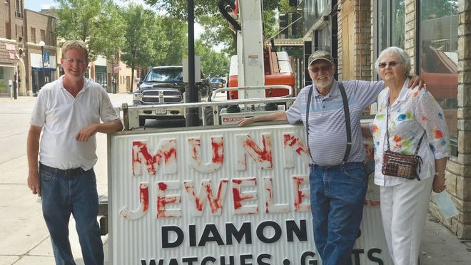 Fournet Building owner Jeff Evers is pictured with Ivan and Lala Fisher, and the former Munn's Jewelry sign that was taken down last week and given to the Fishers