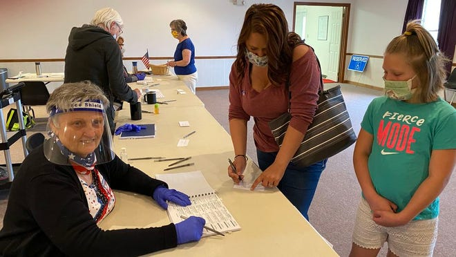 Clerk Debbie Young wore red, white and blue clothes, gloves and a face shield as she worked the poll at Grace Bible Church in Antrim Township, where voters in Tuesday's primary election included Michelle Brechbiel, who was accompanied by her 8-year-old daughter, Brooke. SHAWN HARDY/ECHO PILOT