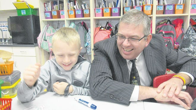 New Albany-Plain Local Superintendent Michael Sawyers, pictured with second-grader Sam Trempe in December 2017, apologized to parents during a June 8 school board meeting for any alarm caused by an online article from a technology website that said the district was implementing a student-surveillance system to comply with COVID-19 coronavirus safety measures.