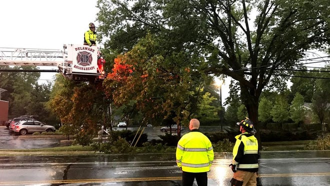 Following a Sept. 7 windstorm, Delaware firefighters use a ladder truck to remove a large broken tree limb that came to rest on utility lines on East Central Avenue near Grady Memorial Hospital. The Labor Day storm knocked out power to thousands, felled trees and produced tornado warnings across Delaware County, though no tornadoes were confirmed to have touched down.