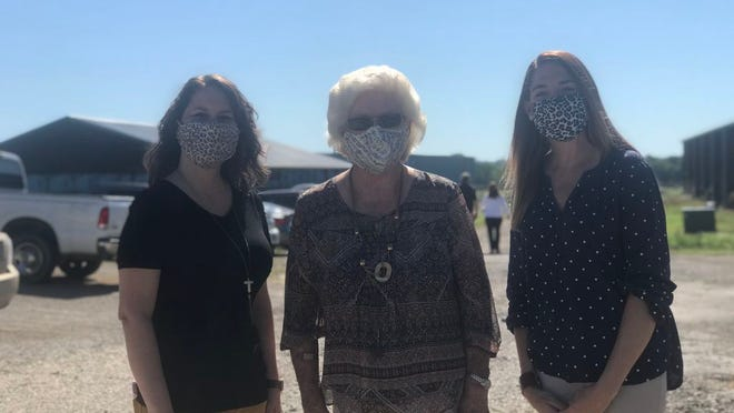 Paris residents Tonya Baumgartner, Jewell White and Shawna Stengel pose for a picture sporting their printed fashion face masks.