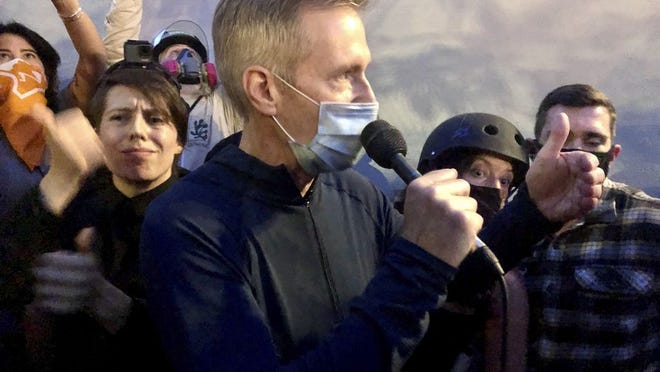 Mayor Ted Wheeler speaks to people gathered in downtown Portland, Ore., Wednesday, July 22, 2020. Wheeler faced a hostile crowd of protesters, who screamed at and sharply questioned him as he tried to rally demonstrators who have clashed repeatedly with federal agents sent in by President Donald Trump to quell ongoing unrest in the city.