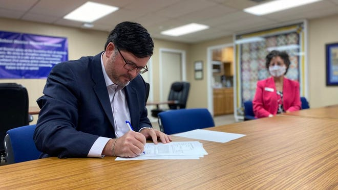Michael Considine, Vice President of Customer Service for Entergy Arkansas, signs the new solar energy contract with Jessieville School District, while the district's superintendent, Melissa Speers, looks on.