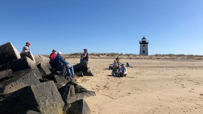 The walking group sits on rocks and the sand, socially distant, for a relaxing lunch. Long Point Light is in the background.