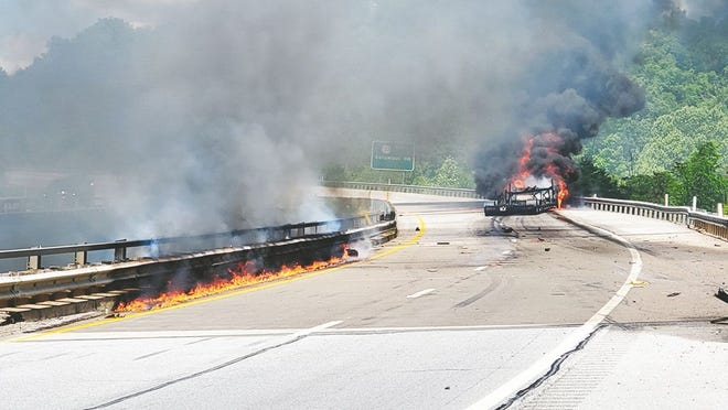 A semi-truck caught on fire after striking the fuel tank on a bridge on I-77.